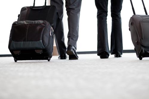 Zwei Geschäftsleute gehen am Flughafen mit einem Koffer